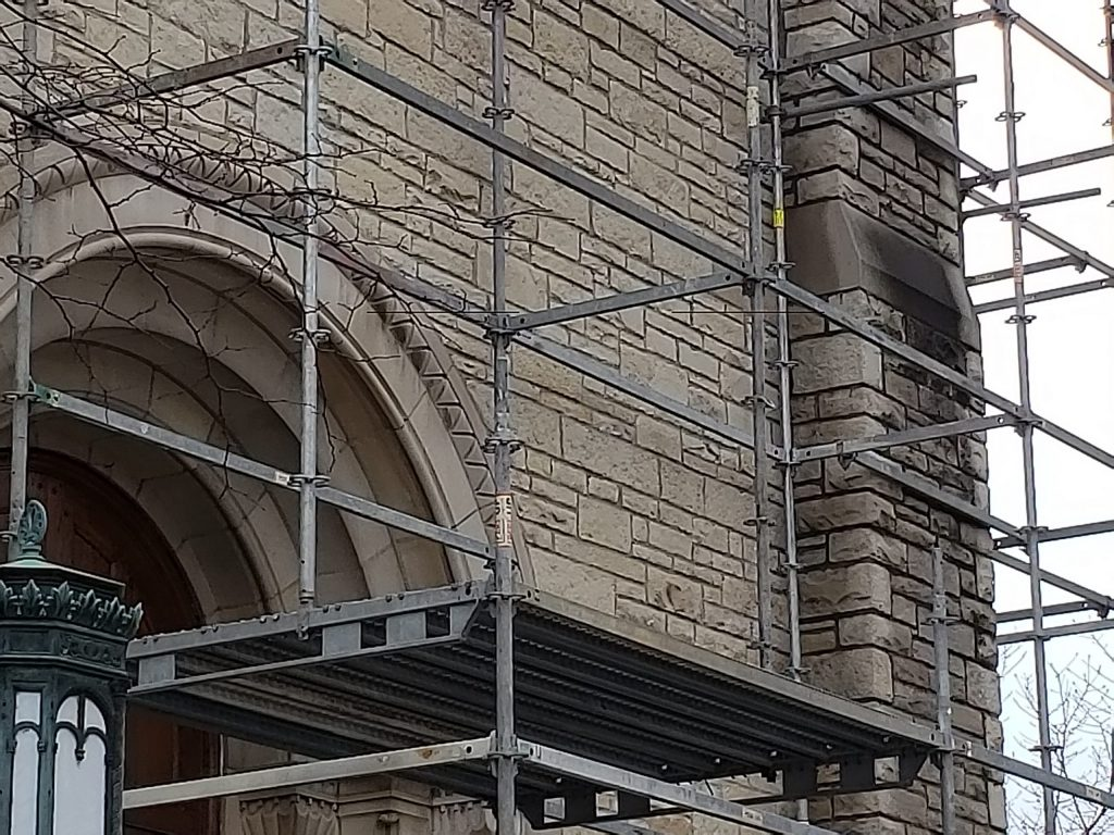 tuckpointers set up to work on a church's masonry